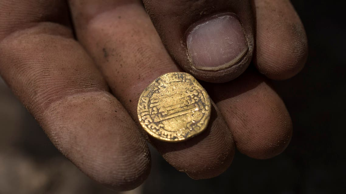 Israeli archaeologist Shahar Krispin displays a gold coin that was discovered at an archeological site in central Israel, Tuesday, Aug 18, 2020. (AP)