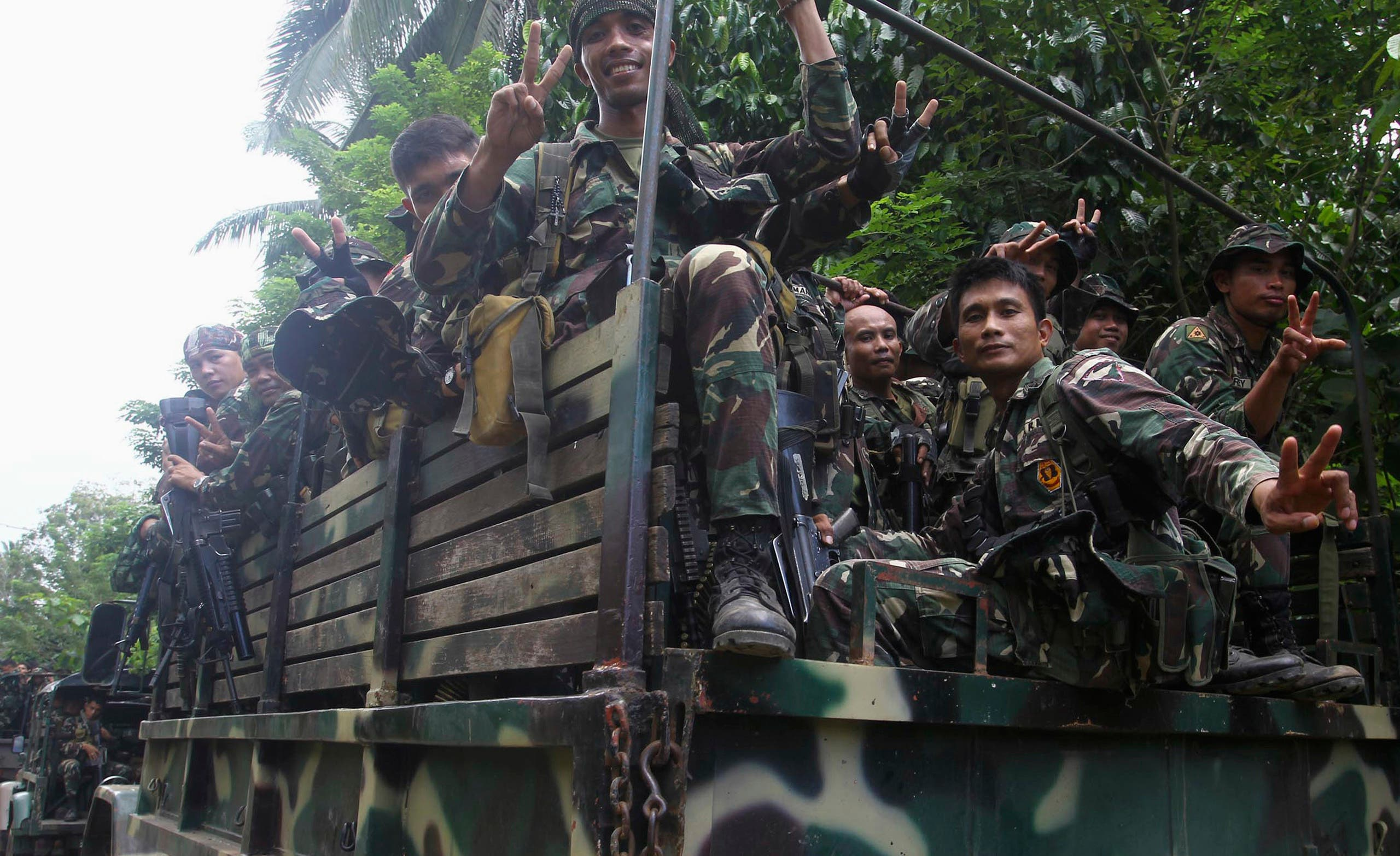 Soldiers gesture aboard a military truck as they are deployed to remote villages in Jolo, Sulu southern Philippines October 17, 2014 after hostages were captured by Abu Sayyaf militants. (Reuters)