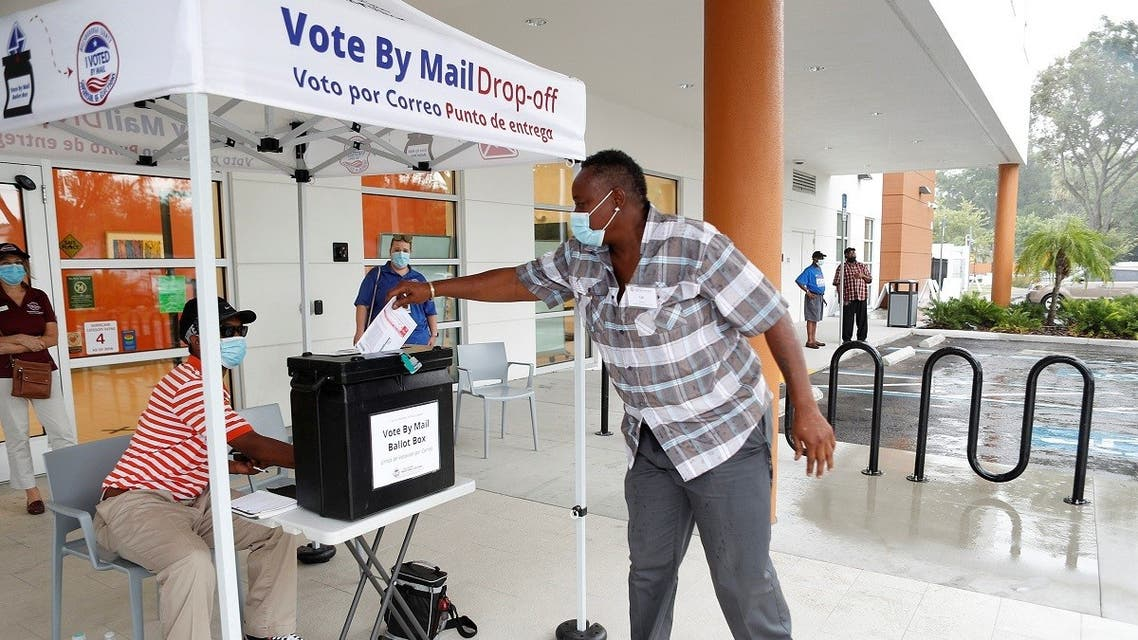 A poll worker casts a mail-in ballot for a disabled driver on the last day of early voting for the US presidential election, Florida, Aug. 16, 2020. (Reuters)