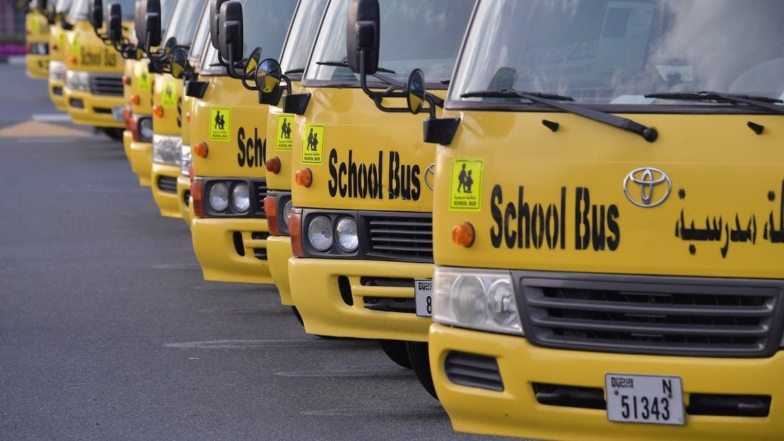 A picture taken on March 15, 2020 shows school buses parked outside a closed school in Dubai. (AFP)