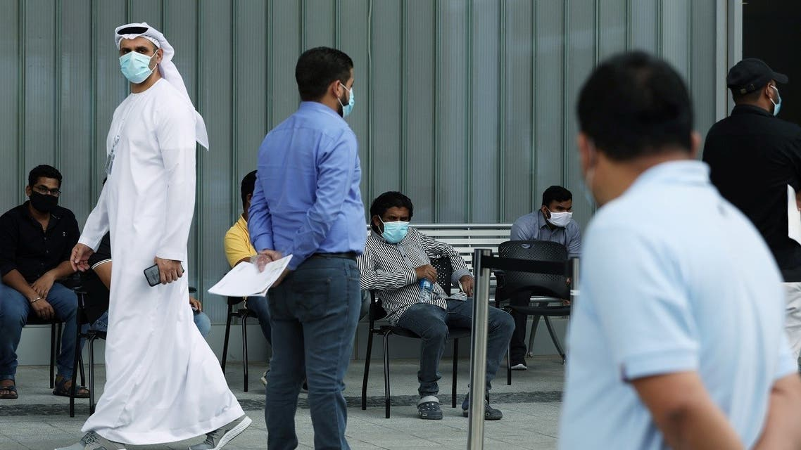 A member of hospital staff watches over people queuing to be tested, amid the coronavirus outbreak, at the Cleveland Clinic hospital in Abu Dhabi, UAE, April 20, 2020. (Reuters)