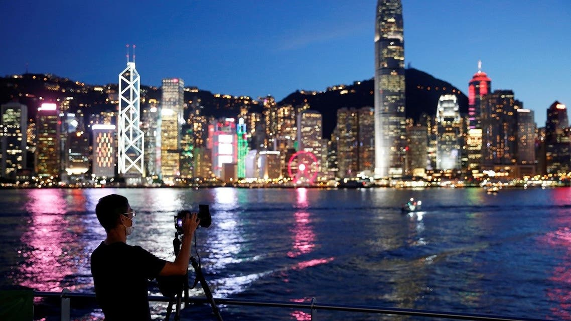 A man wearing a protective face mask takes a photo of the sunset at Tsim Sha Tsui waterfront as skyline buildings stand across Victoria Harbor following the coronavirus disease (COVID-19) outbreak in Hong Kong. (File photo: Reuters)