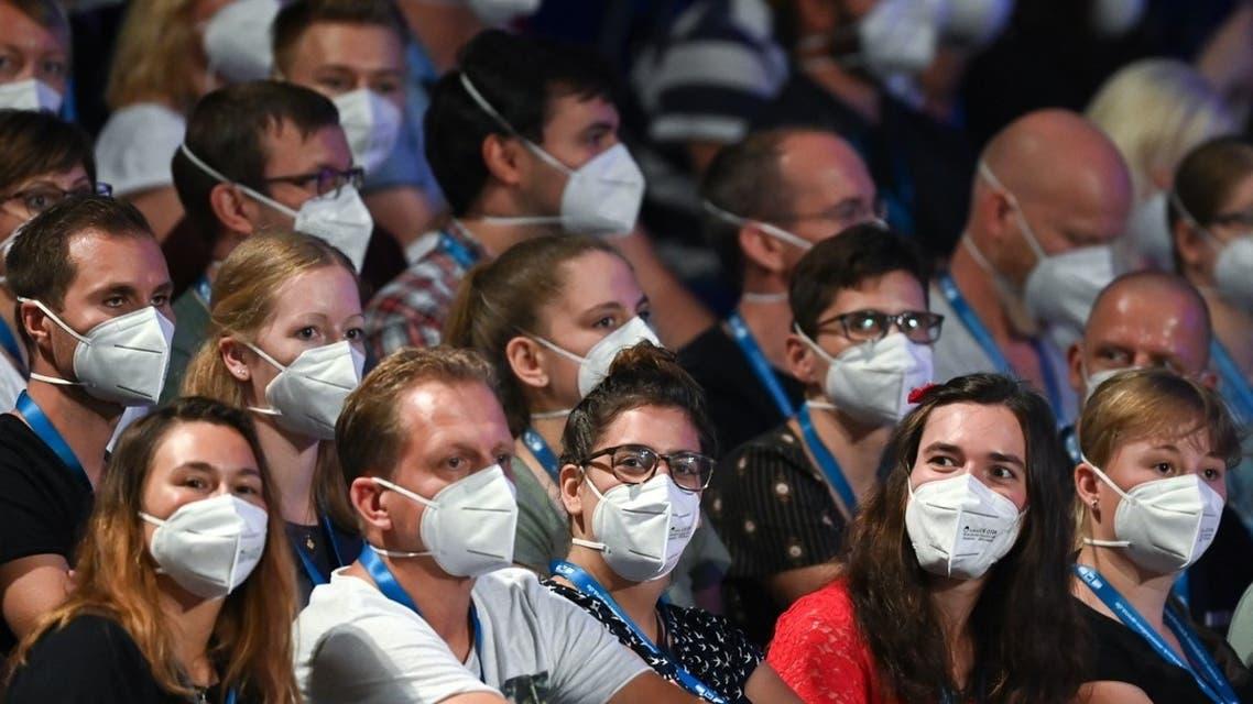 People wear face masks as German pop singer Tim Bendzko performs on stage at the Arena in Leipzig, eastern Germany. (AFP)