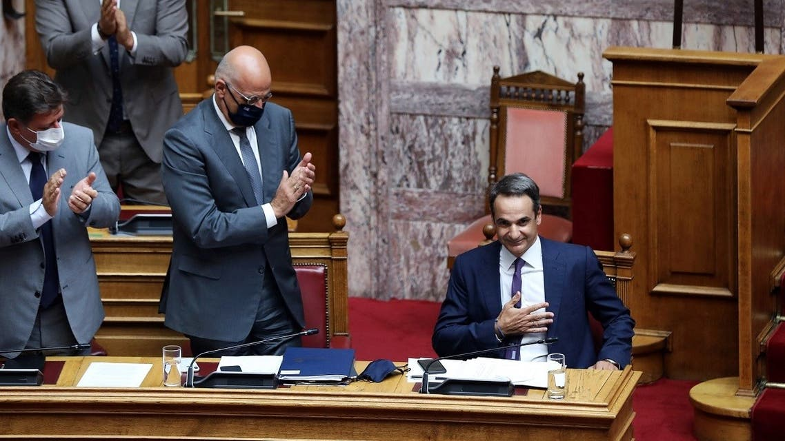 Greek Prime Minister Kyriakos Mitsotakis is applauded by his lawmakers and ministers after his speech during a parliamentary session on an accord which defines maritime boundaries with Egypt in the Mediterranean, at the parliament in Athens, Greece, August 26, 2020. (Reuters)