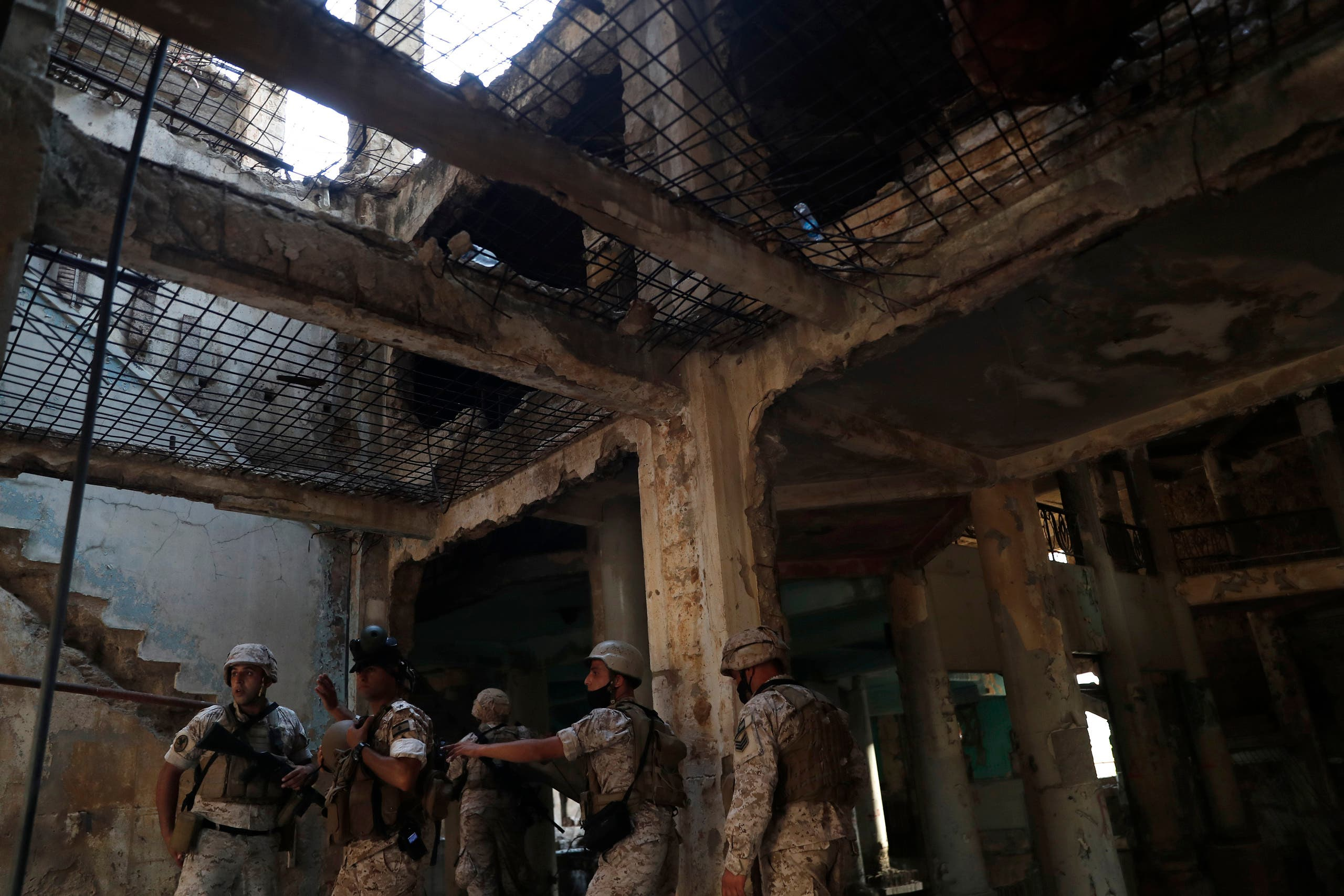 Lebanese soldiers gather inside a damaged building as they prepare to attack the anti-government protesters, who are trying to reach the Parliament building, during a protest against the political elites and the government, in Beirut, Lebanon, Saturday, Aug. 8, 2020. (AP)