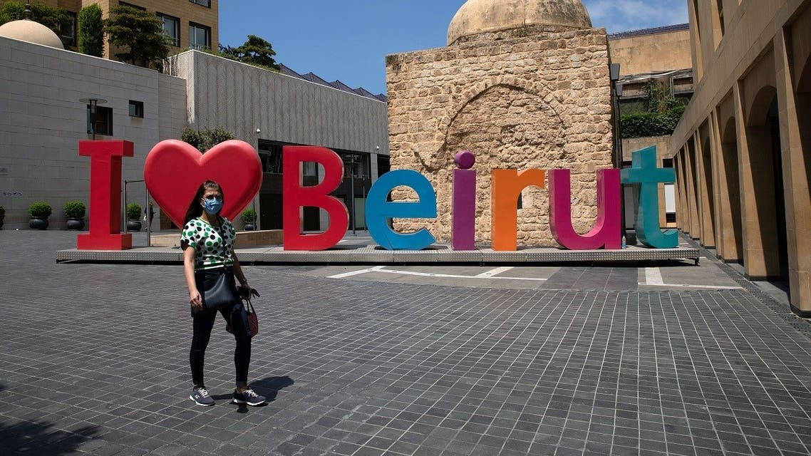 2020-08-A woman wearing a face mask walks past an I love Beirut sign, near a shopping district, as Lebanon imposed a partial lockdown for two weeks starting on Friday in an effort to counter the spread of the coronavirus disease (COVID-19), which have spiralled since the catastrophic explosion at Beirut port, Lebanon August 21, 2020. REUTERS-CORONAVIRUS-LEBANON-LOCKDOWN