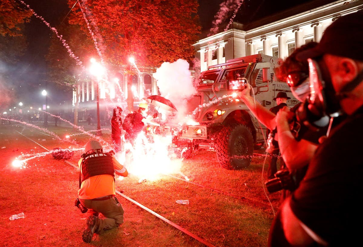 Flares go off in front of a Kenosha Country Sheriff Vehicle as demonstrators take part in a protest following the police shooting of Jacob Blake, a Black man, in Kenosha, Wisconsin, US, on August 25, 2020. (Reuters)