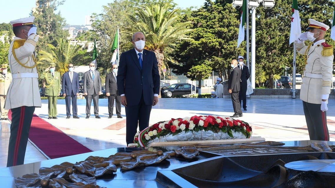 Algeria's President Abdelmajid Tebboune observing a moment of silence during a ceremony to lay to rest the remains of 24 resistance fighters, returned from Paris after more than a century and a half, on the 58th anniversary of Algeria's independence from France, in the capital Algiers on July 5, 2020. (AFP/ Ho/Algerian Presidency Press Service)