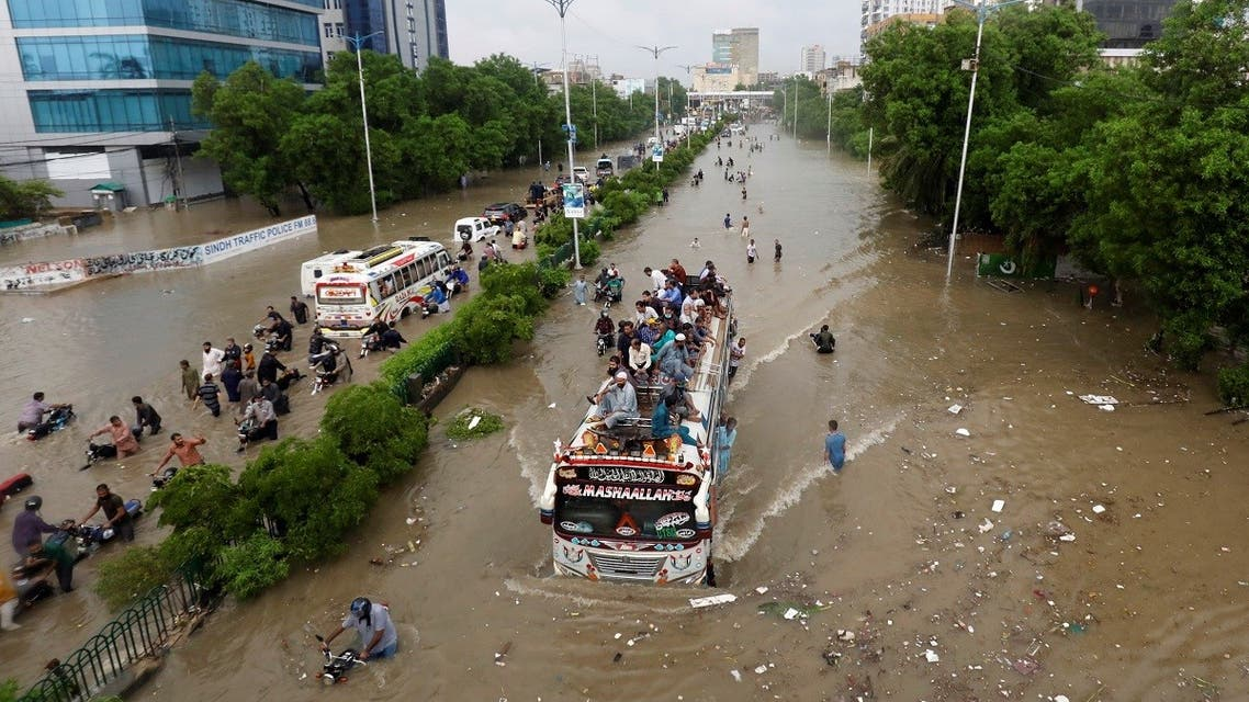 People sit atop a bus roof while others wade through the flooded road during monsoon rain in Karachi. (Reuters)