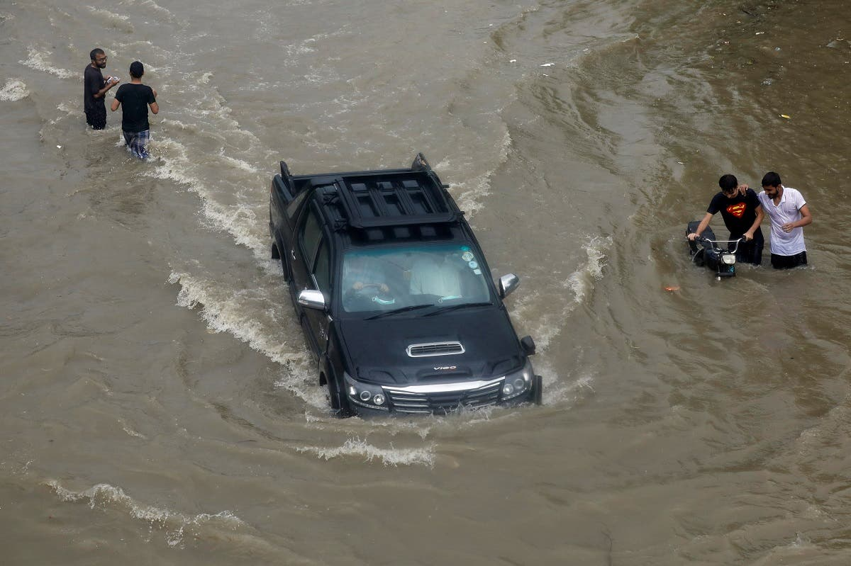 A vehicle passes through the flooded street during monsoon rain, as the outbreak of the coronavirus disease (COVID-19) continues, in Karachi. (Reuters)