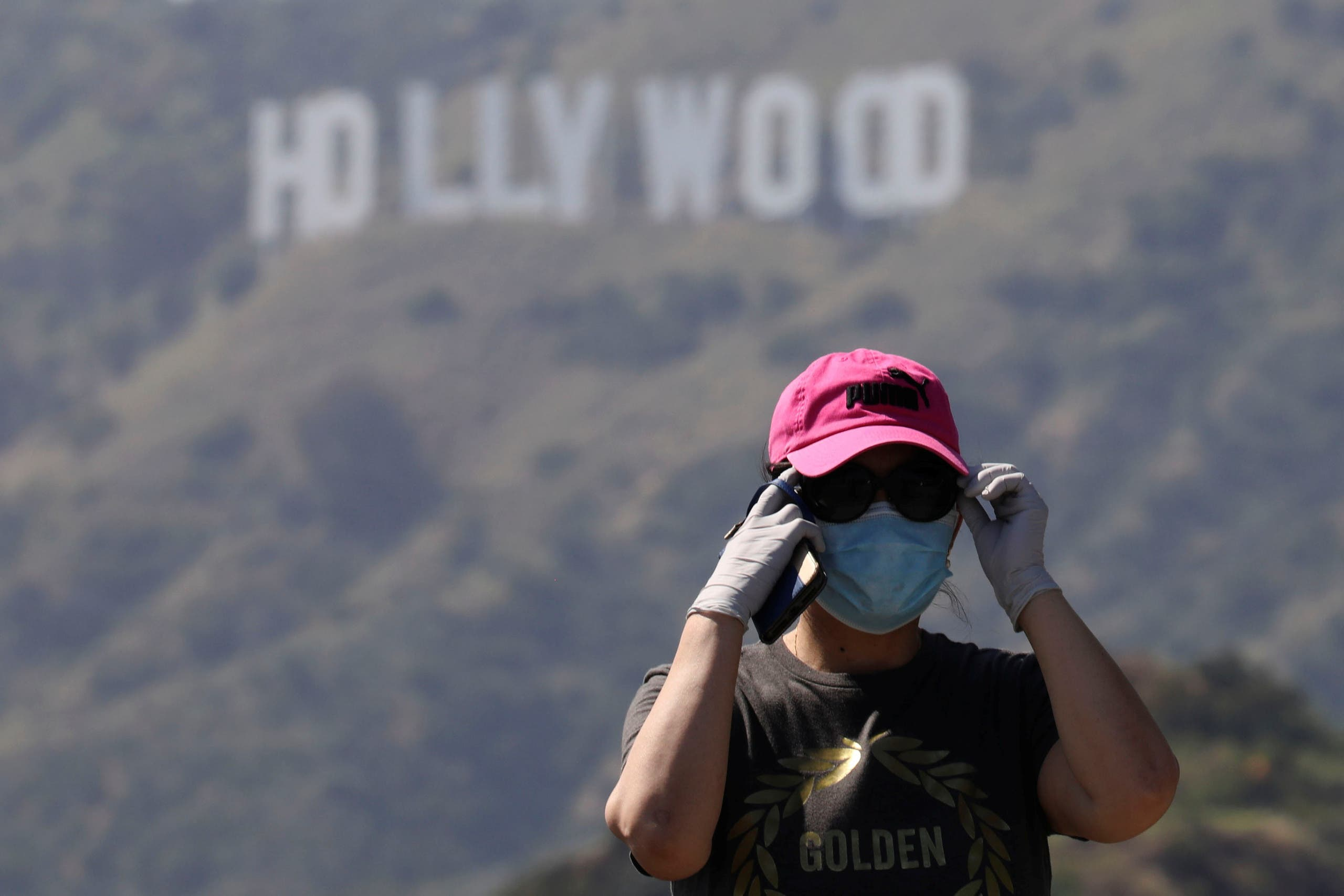 A person wearing a face mask and gloves adjusts glasses while taking photos of the Hollywood sign in Los Angeles, California, U.S., May 9, 2020. (Reuters)