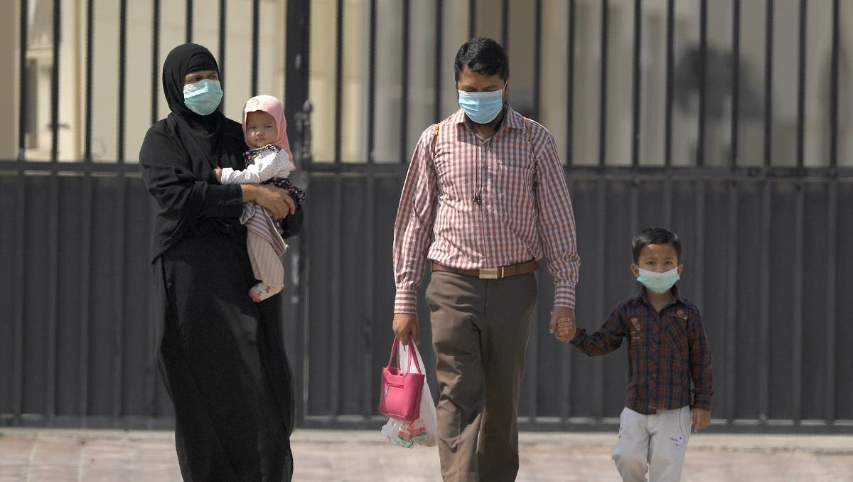 Parents wearing protective masks and their children leave a school they found closed due to the COVID-19 coronavirus, after arriving to register for the new academic year, in Sharjah. (File photo: Reuters)