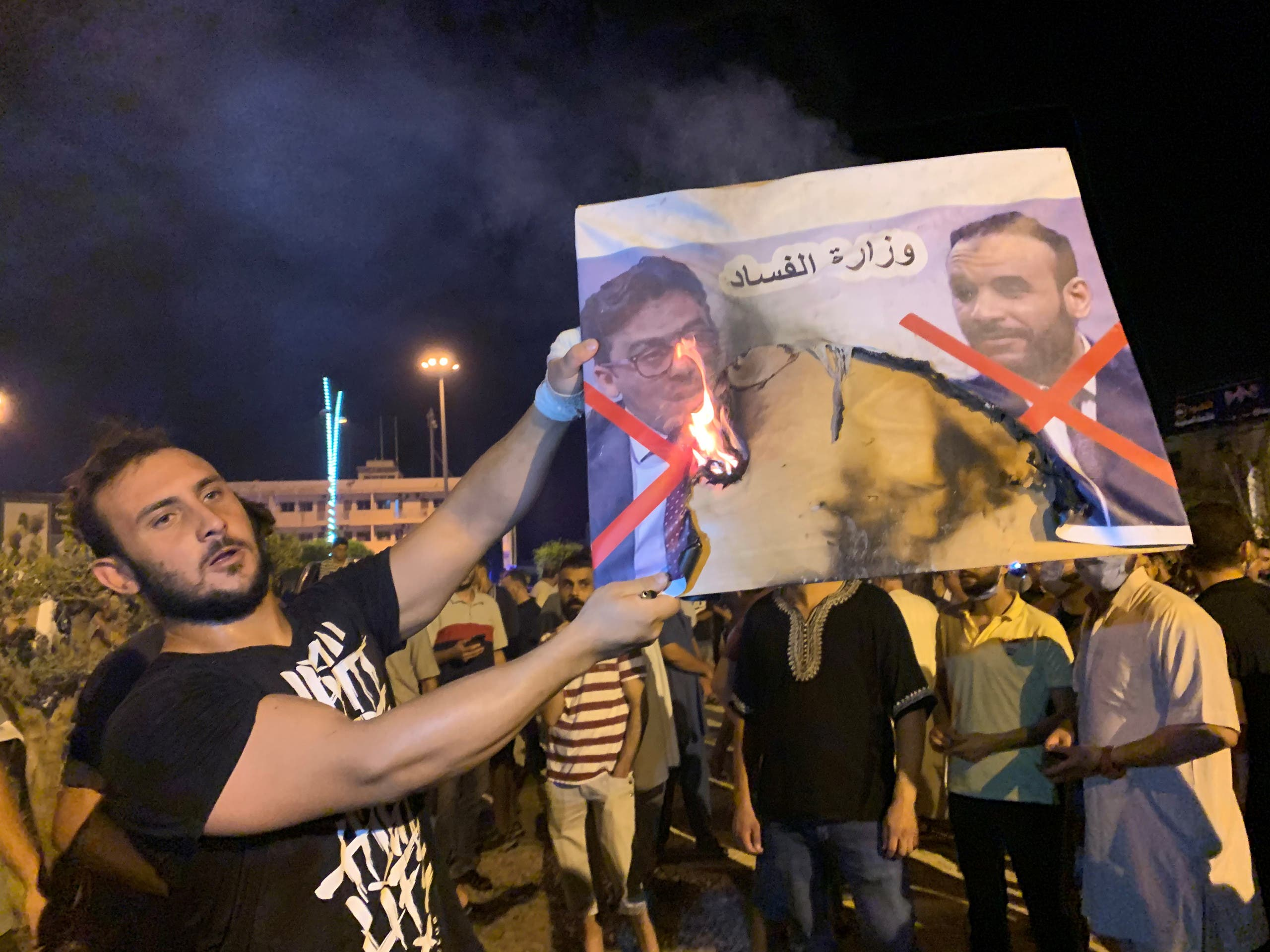 A Libyan protester burns an image of Libyan officials as he protests over announcement of suspension of the Interior Minister Fathi Bashagha during an anti-government protest in Misrata, Libya August 29, 2020. (Reuters)