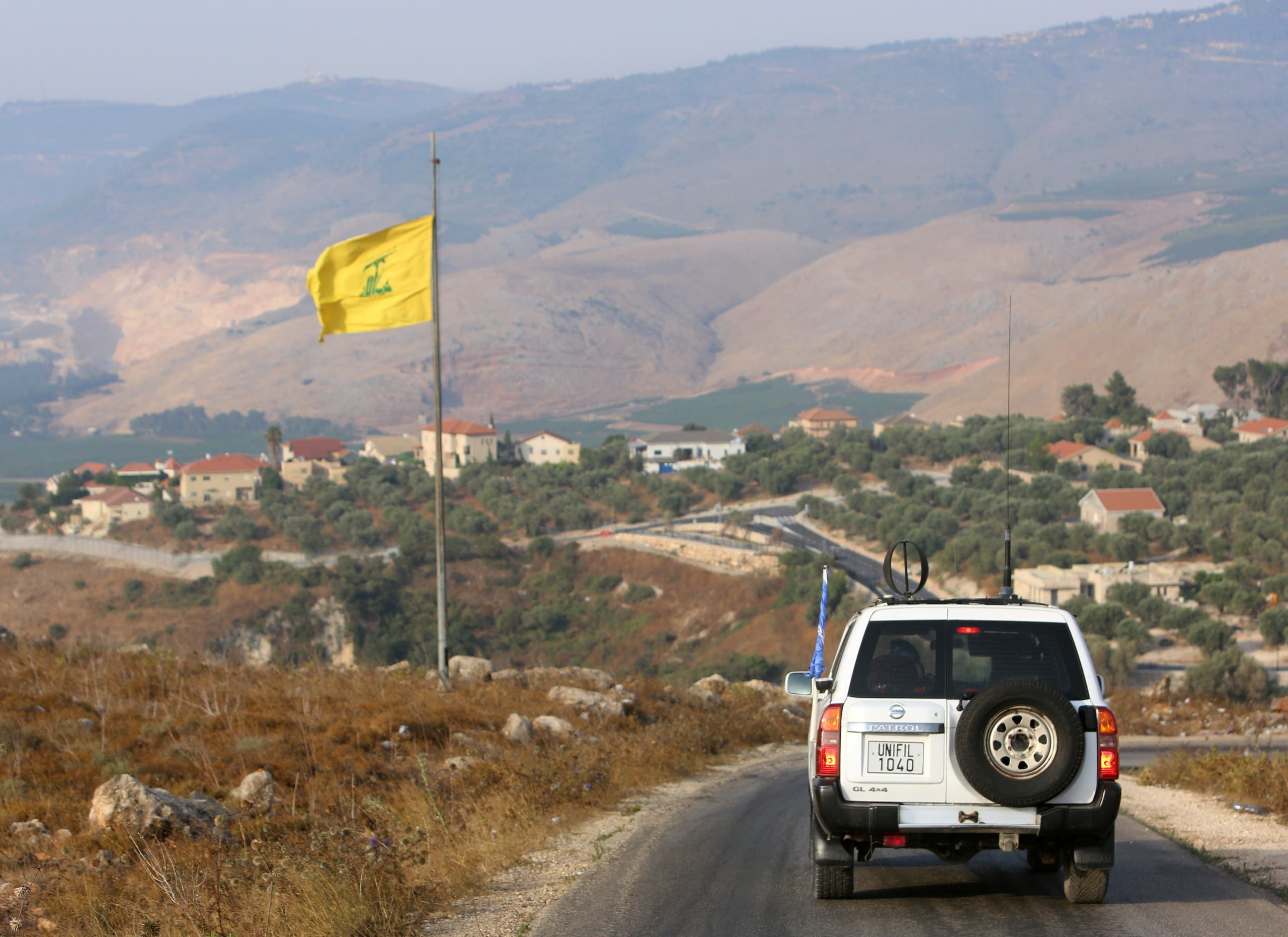 A UN peacekeepers (UNIFIL) vehicle drives past a Hezbollah flag in the southern Lebanese village of Khiam, near the border with Israel, Lebanon. (File photo: Reuters)