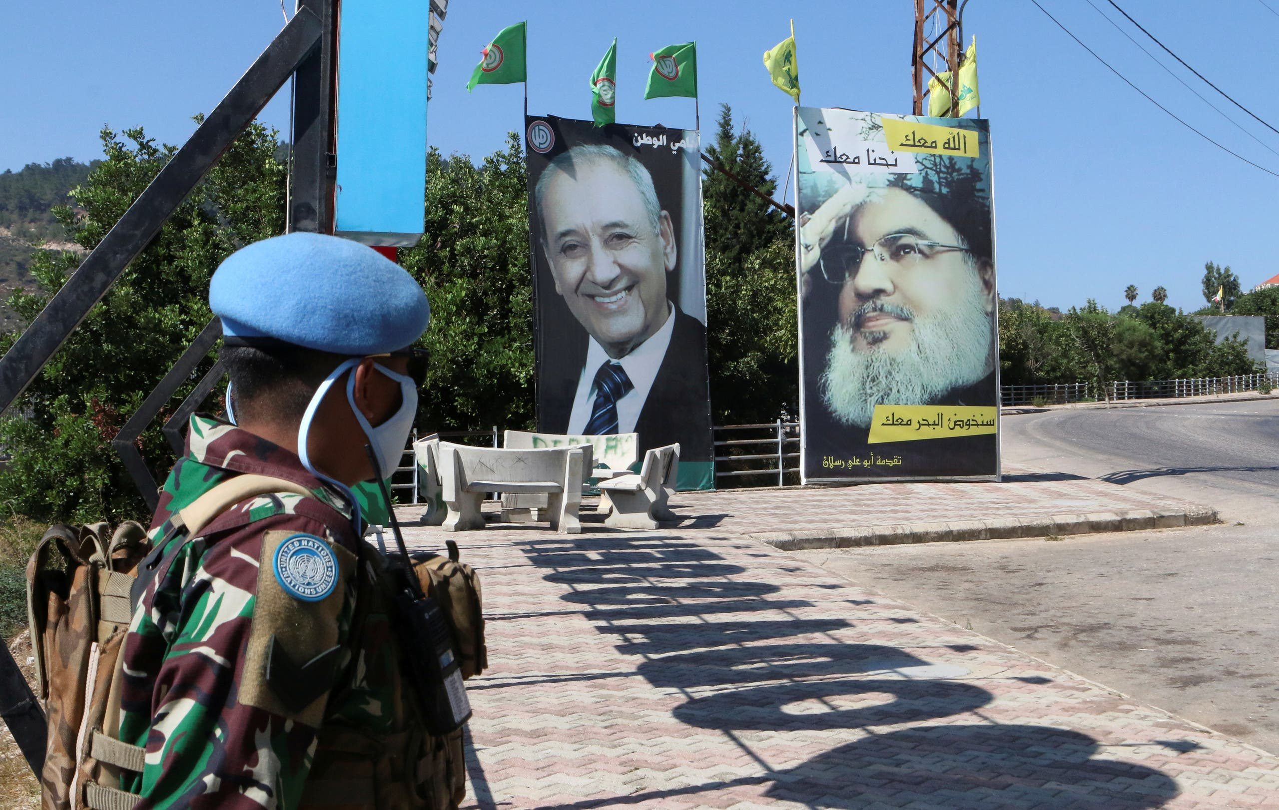 A United Nations peacekeeper (UNIFIL) stands near a poster depicting Lebanon's Hezbollah leader Sayyed Hassan Nasrallah, in Adaisseh village, near the Lebanese-Israeli border, Lebanon August 7, 2020. (Reuters)