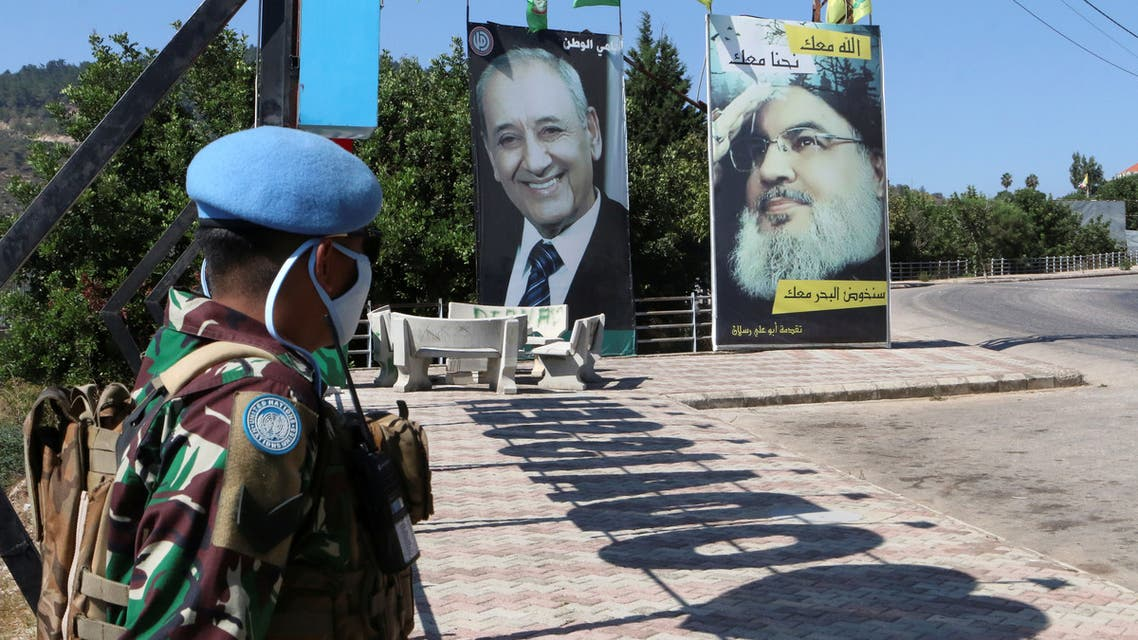 UNIFIL soldiers stand near a poster of Hezbollah leader Hassan Nasrallah and Speaker Nabih Berri, near the Lebanese-Israeli border, Aug. 7, 2020. (Reuters)