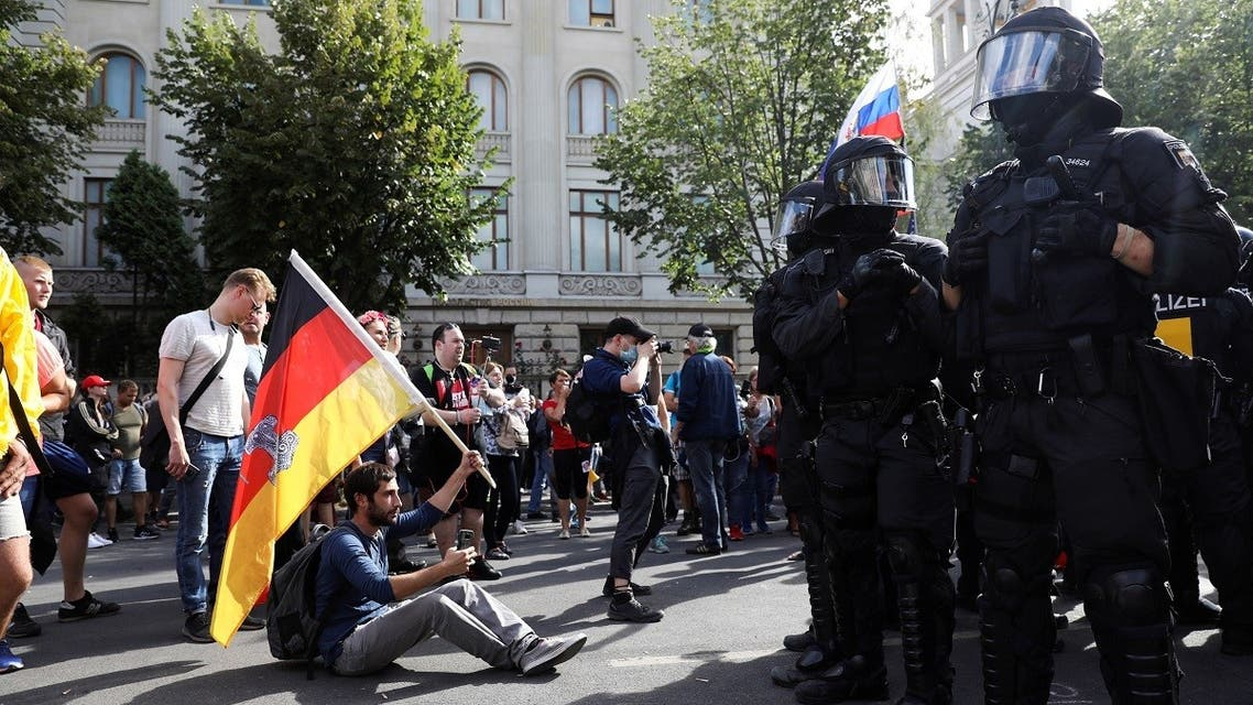A demonstrator sits in front of police officers as he attends a rally against the government's restrictions following the coronavirus in Berlin, Germany, August 29, 2020. (Reuters)