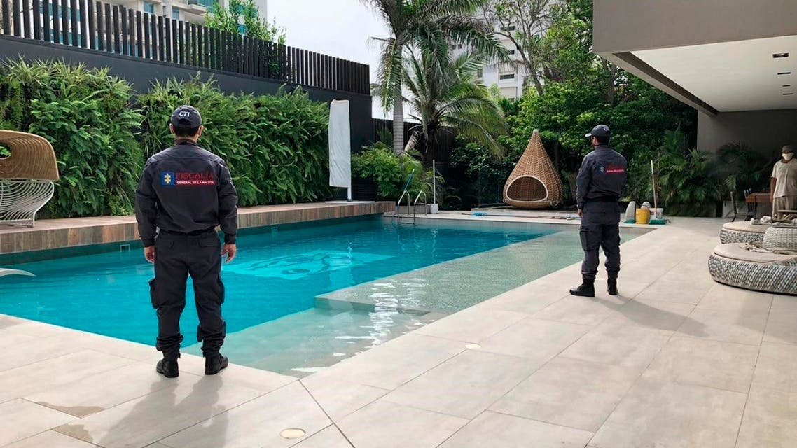 officials pose with their backs to the camera by a pool on a property allegedly belonging to Alex Saab in Barranquilla, Colombia. (AP)
