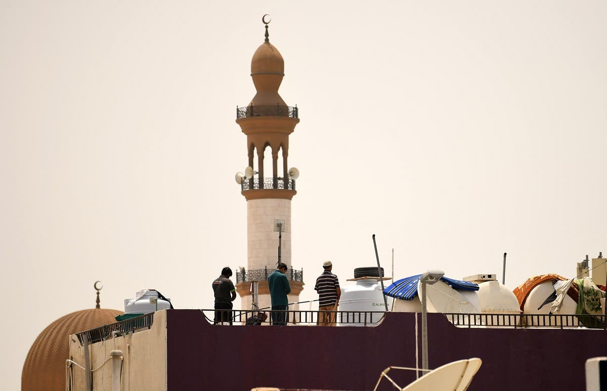 Workers pray on the roof of a residential building near a mosque during a curfew imposed to prevent the spread of coronavirus disease (COVID-19) in the Gulf Emirate of Dubai, on April 21, 2020. (AFP)