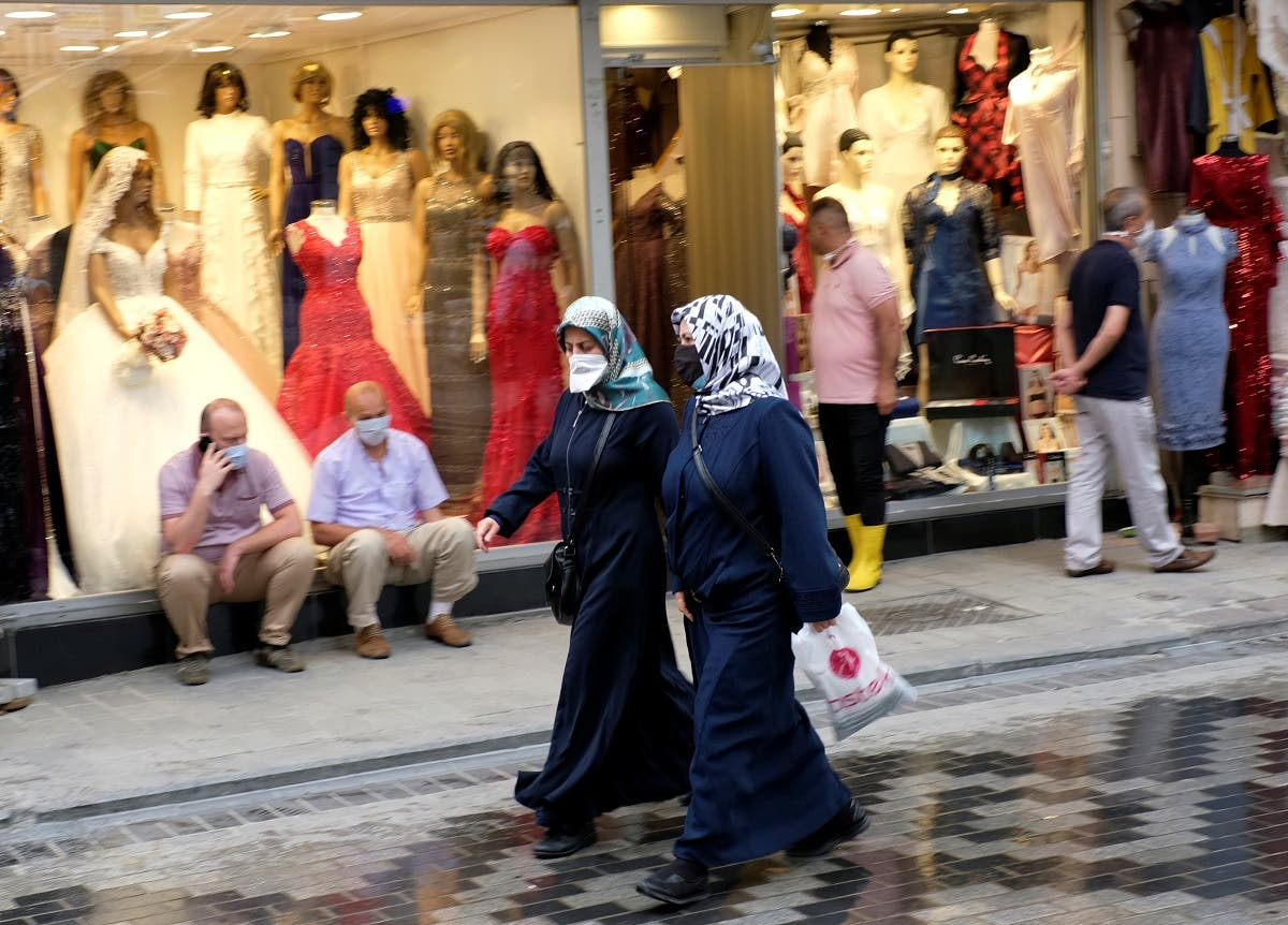 Women wearing protective face masks walk past by a shop, amid the coronavirus outbreak, in Istanbul, Turkey June 23, 2020. (Reuters)