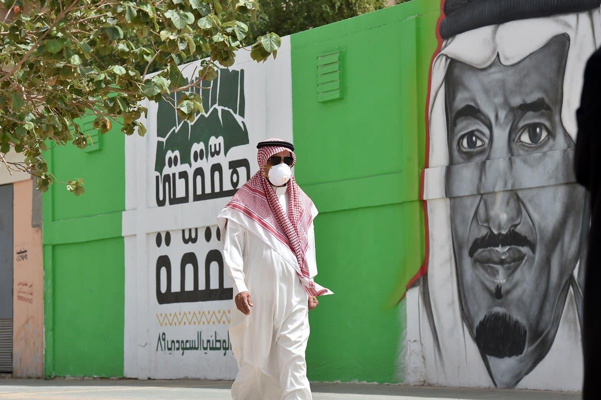 A Saudi man, wearing a protective mask as a precaution against COVID-19 coronavirus disease, walks past a mural showing the face of King Salman bin Abdulaziz. (File photo: AFP)