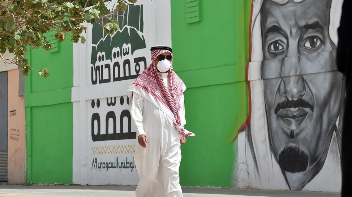 A Saudi man, wearing a protective mask as a precaution against COVID-19 coronavirus disease, walks past a mural showing the face of King Salman bin Abdulaziz. (File photo: AFP)