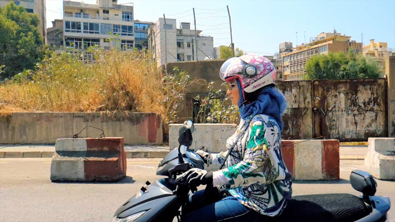 Carine Karazi drives a motorbike used by her and her mother's women-only taxi service. (Supplied)