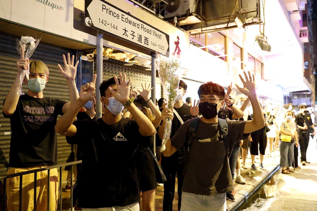 Pro-democracy protesters raise their hands up as a symbol of Five demands, not one less during a protest outside the Prince Edward station to mark one year since authorities stormed the underground station at Mong Kok in Hong Kong, China, on August 31, 2020. (Reuters)