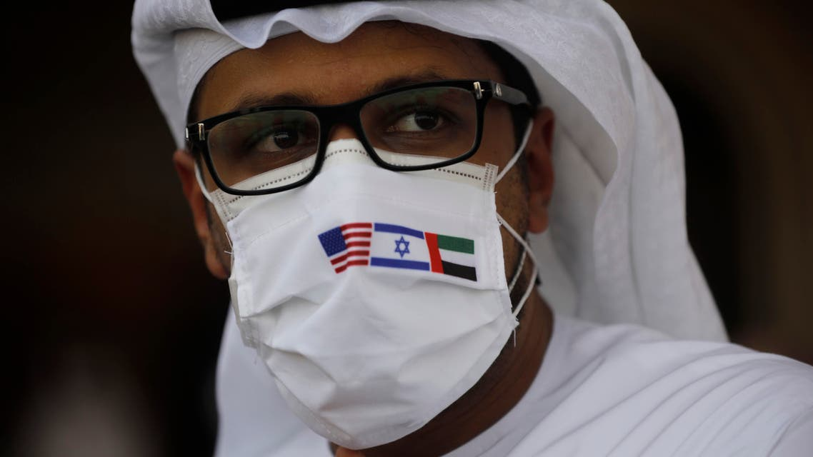 A man wearing a mask bearing the national flags of America, Israel and United Arab Emirates  in Abu Dhabi on Aug. 31, 2020. (AP)