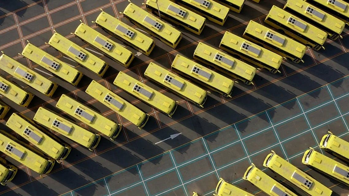 A drone image taken on April 27, 2020, shows school buses parked in a lot in the Emirate of Dubai, during the coronavirus pandemic. (File photo: AFP)