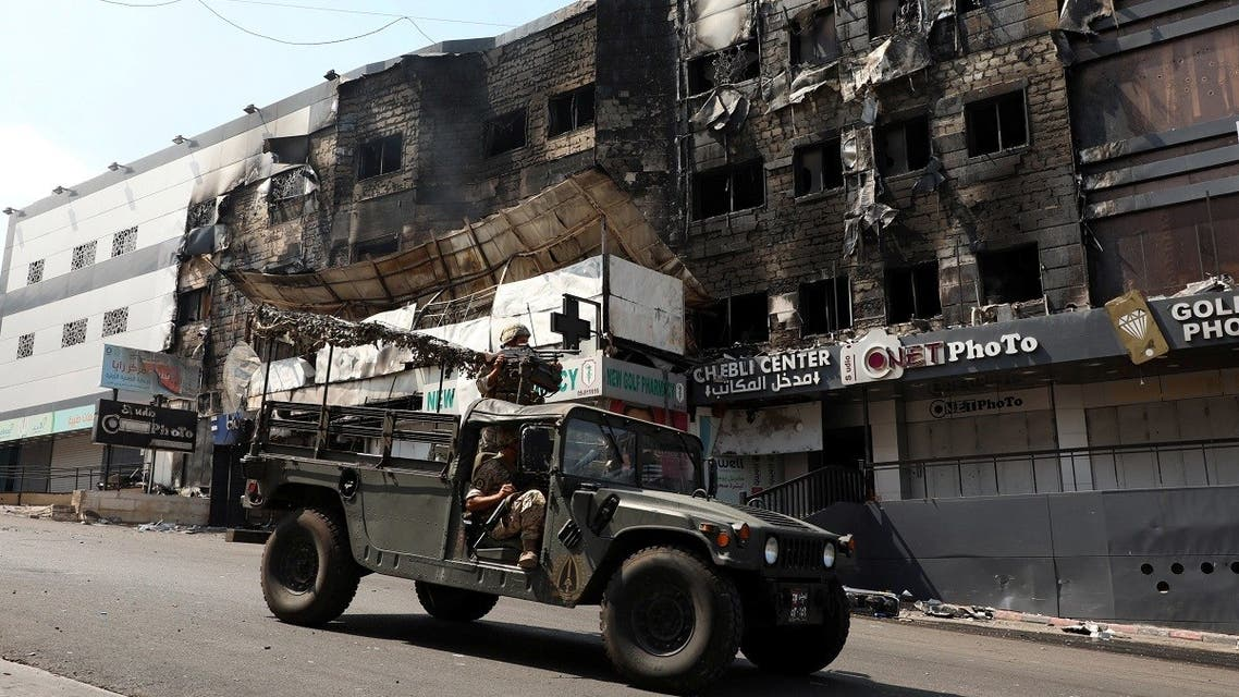 A Lebanese army patrol near burnt shops in the aftermath of clashes south of Beirut, Aug. 28, 2020. (Reuters)