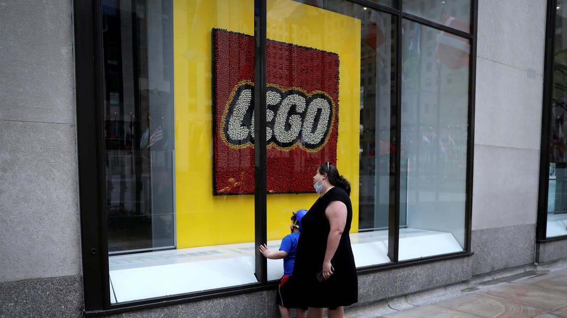A woman and a child look through the windows of the closed Lego store at Rockefeller Center on 5th Avenue, during the outbreak of the coronavirus, in Manhattan, New York city, New York, US, May 11, 2020. (Reuters)