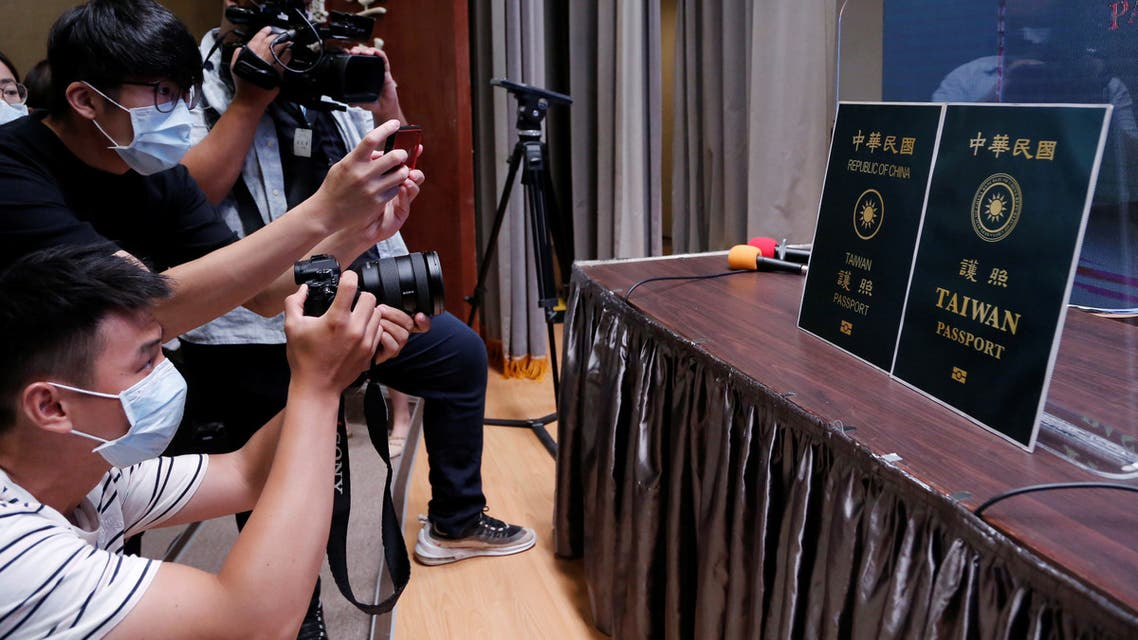 Members of the media take photos of paper cut outs of the old and new (R) Taiwan passport displayed in Taipei, Taiwan, September 2, 2020. REUTERS/Ann Wang