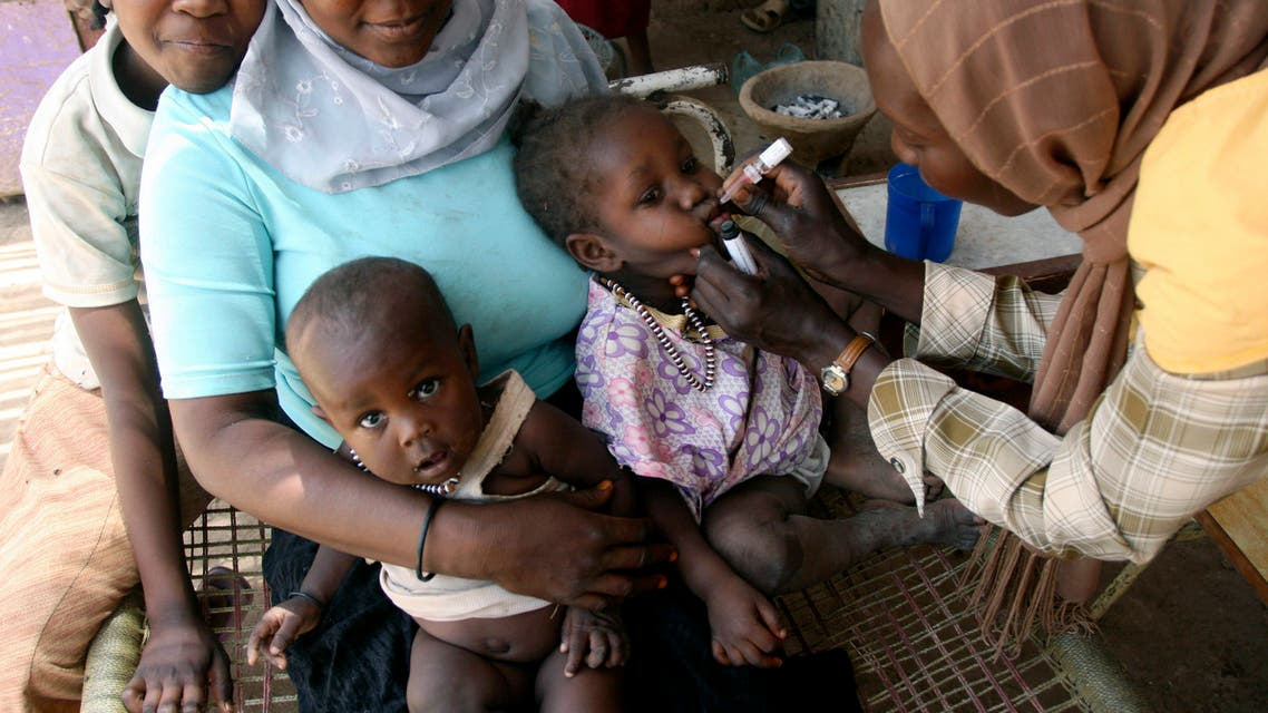 A social worker administers polio drops to a child at an Angloa camp in Khartoum, March 27, 2007. The government sponsored campaign targets children under the age of 5. REUTERS/Mohamed Nureldin Abdalla (SUDAN)