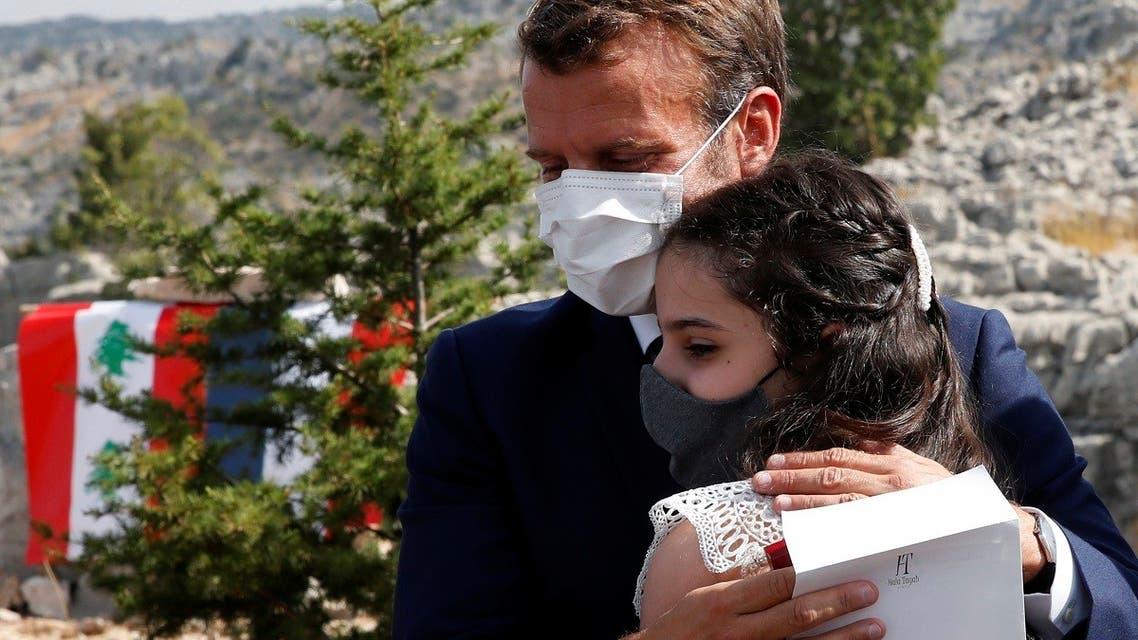 French President Emmanuel Macron hugs blast victim Tamara Tayah after planting a cedar in Lebanon, Sept. 1, 2020. (AP)