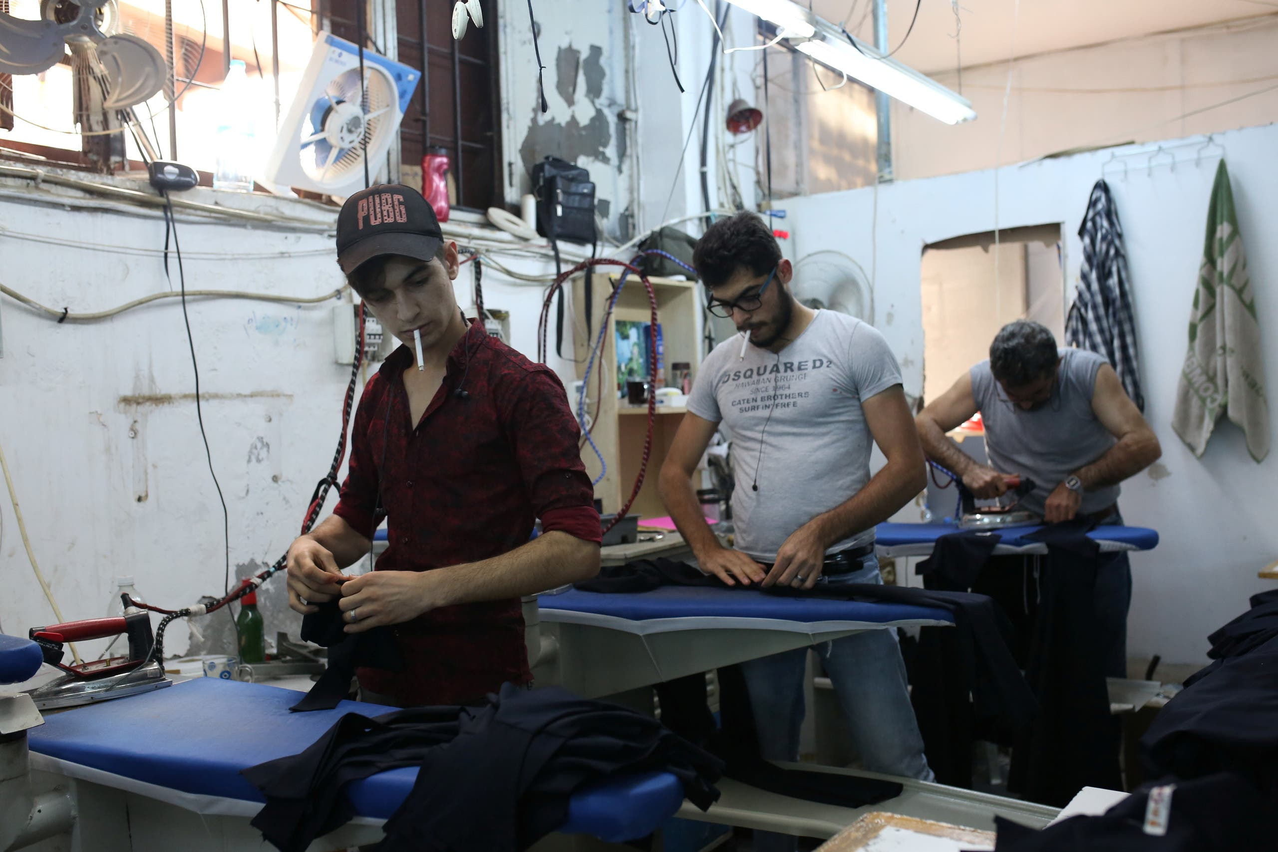 Syrian refugee men work at a textile workshop as day laborer in Istanbul, Turkey, June 20, 2019. (Reuters)