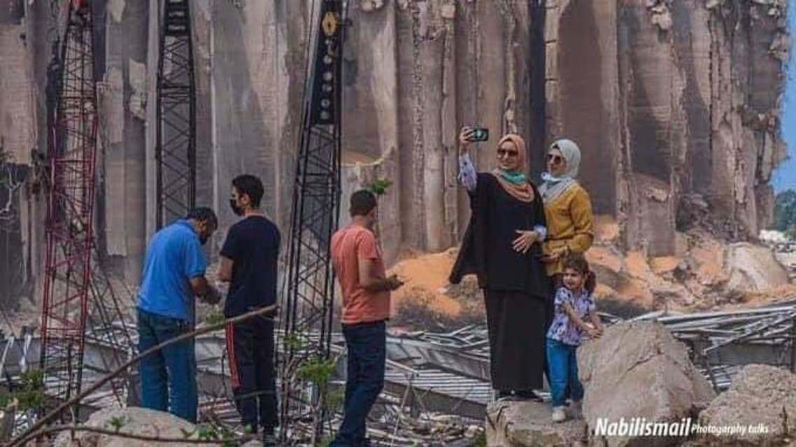 A photograph showing two people taking a selfie in front of the Beirut blast. (Rami Chakroun, Twitter)