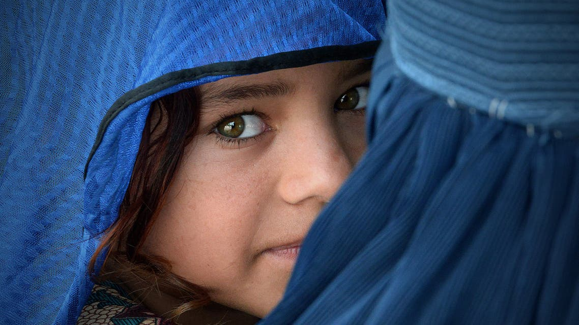 An Afghan woman carries her girl during the visit of the United Nations High Commissioner for Refugees, Filippo Grandi (unseen) at the Azakhel Voluntary Repatriation Centre in Nowshera on September 8, 2018. (File photo: AFP)