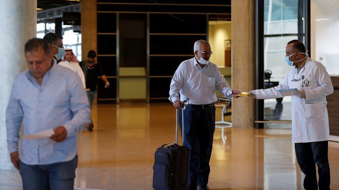 Passengers receive brochures that contain medical tips to prevent coronavirus at Queen Alia International Airport in Amman, Jordan March 4, 2020. (Reuters)