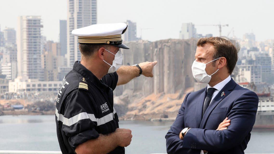 Arnaud Tranchant, left, chief Navy officer for the French helicopter carrier Tonnerre, talks to French President Emmanuel Macron off the port of Beirut on Sept.1, 2020. (AP)