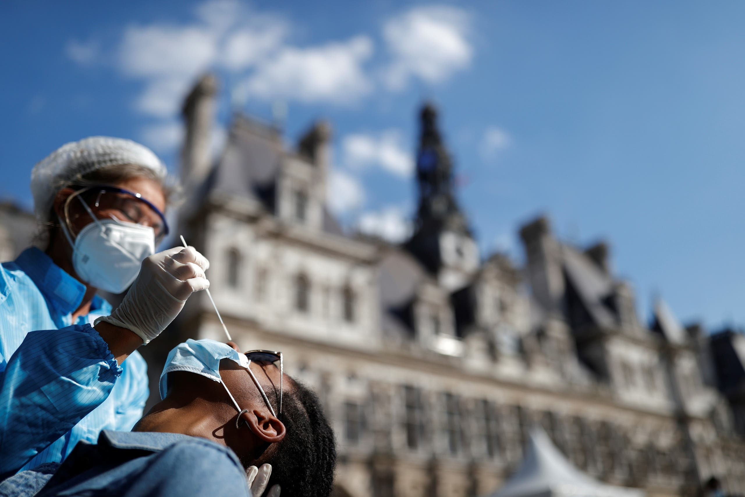 A health worker, wearing a protective suit and a face mask, prepares to administer a nasal swab to a patient at a testing site for the coronavirus disease installed in front of the city-hall in Paris, France, September 2, 2020. (Reuters)