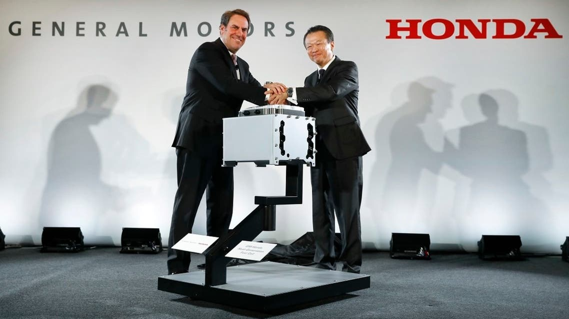 Mark Reuss, General Motors executive vice president of Global Product Development, left, and Toshiaki Mikoshiba, chief operating officer of the North American Region for Honda Motor Co., Ltd., shake hands at a news conference announcing the GM-Honda Next Generation Fuel Cell in Detroit. (AP)
