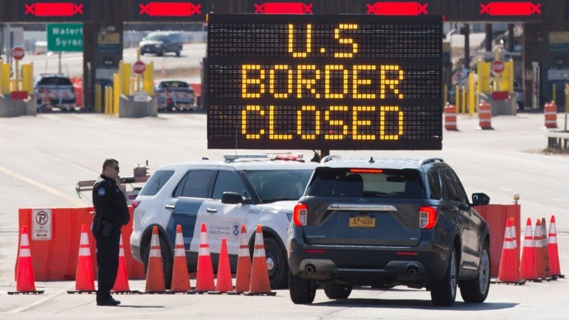 US Customs officers speaks with people in a car beside a sign saying that the US border is closed at the US/Canada border in Lansdowne, Ontario, on March 22, 2020. (AP)