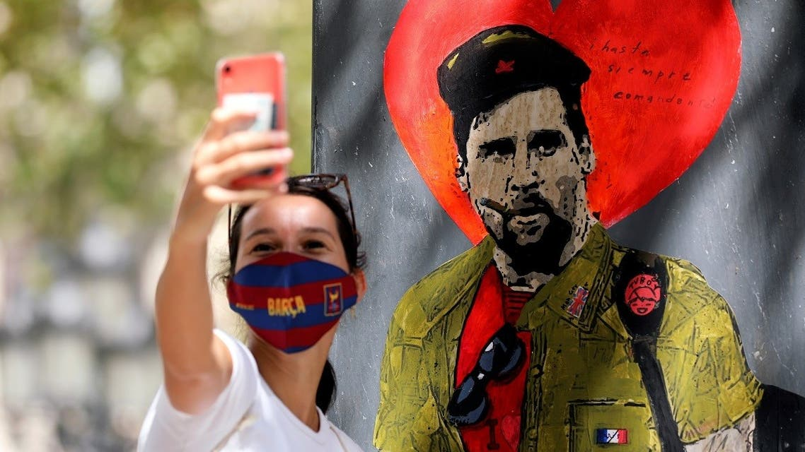 A woman takes a selfie with a mural of Lionel Messi dressed as Che Guevara as FC Barcelona's squad arrive for coronavirus disease (COVID-19) test. (Reuters)