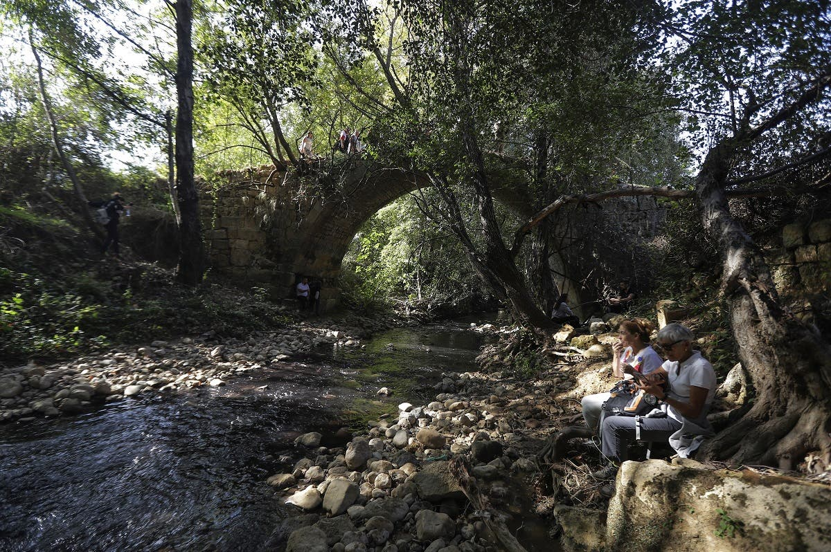 Lebanese protesters take a break by the 'Roman Bridge' during a 20km (12 miles) march in the Bisri Valley, southwest of the capital Beirut on November 22, 2019. (AFP)