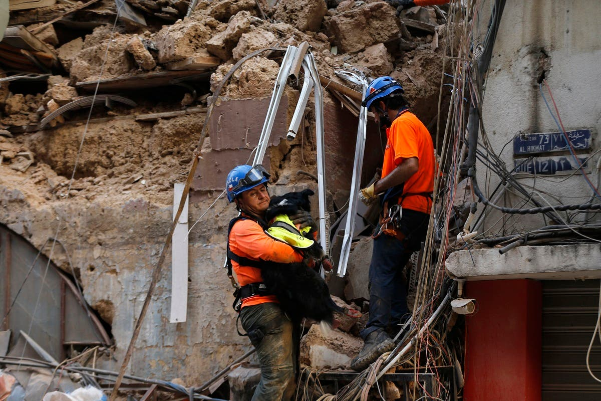 A Chilean rescuer holds a rescue dog as they search in the rubble of a building that was collapsed in Beirut port blast, after getting signals there may be a survivor under the rubble, Beirut, Lebanon, Sept. 3, 2020. (AP)