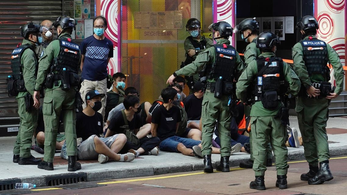 People, sitting on the ground, are arrested by police officers at a downtown street in Hong Kong on Sept. 6, 2020. (AP)