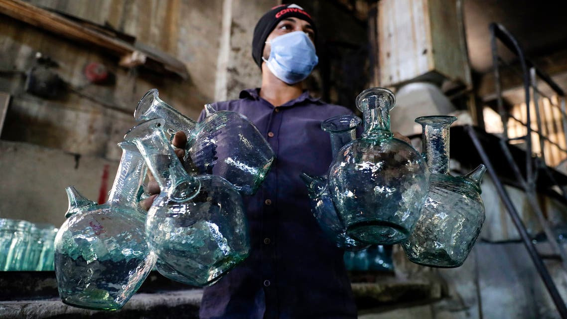 A glassblower forms glass at factory, which is recycling the broken glass as a result of the Beirut explosion, in the northern Lebanese port city of Tripoli on August 25, 2020. The August 4 port explosion ripped through countless glass doors and windows when it laid waste to whole Beirut neighbourhoods, killing at least 190 people and wounding thousands more. Volunteers, non-governmental groups and entrepreneurs salvaged a fraction of the tonnes of broken glass that littered the streets, some of it through recycling at Wissam Hammoud's family's glass factory.