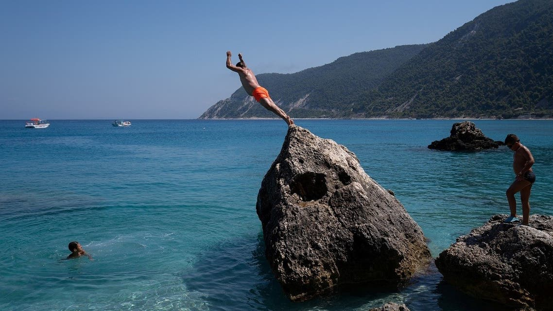 A man dives at Agios Nikitas beach, following the easing of measures against the spread of the coronavirus disease (COVID-19), on the island of Lefkada. (Reuters)