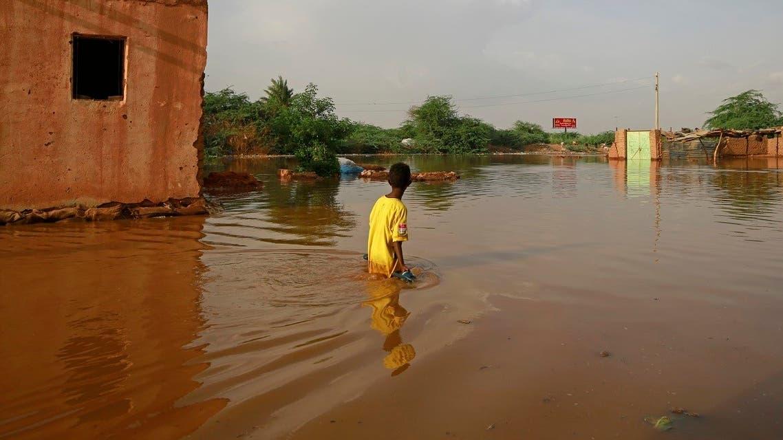 A Sudanese boy wades through a flooded street at the area of al-Qamayir in the capital's twin city of Omdurman. (AFP)